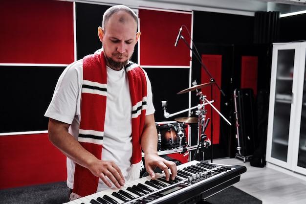 Portret van mannelijke pianist van muzikale groep die synthesizer speelt tegen de achtergrond van oefenbasis
