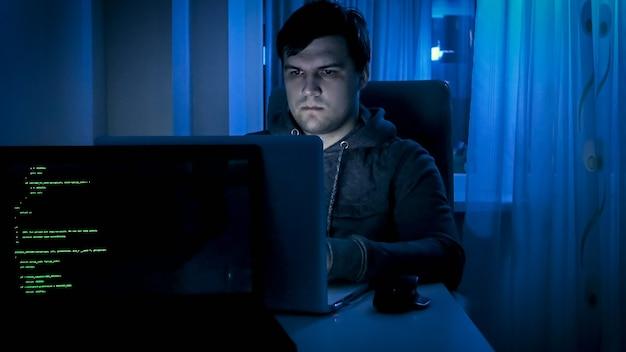 Portret van mannelijke programmeur of hacker die 's nachts op de computer werkt