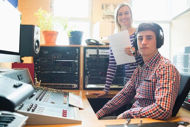 Portret van mannelijke radiogastheer met vrouwelijke werknemer