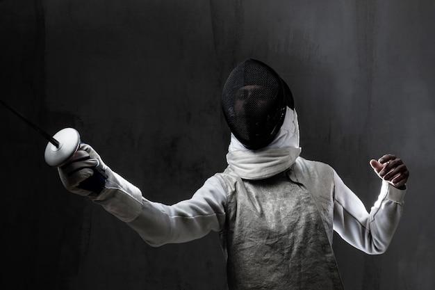 Portret van mannelijke schermer in masker en folie die strijd uitvoeren