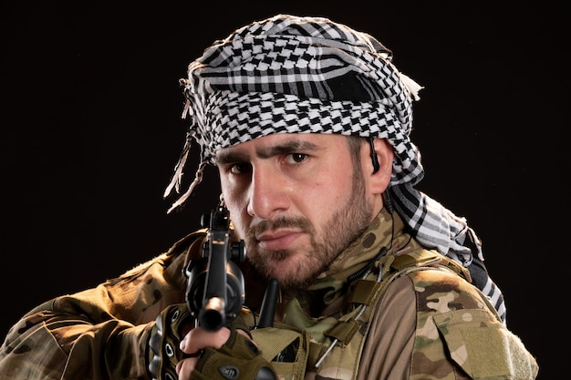 Portret van mannelijke soldaat in camouflage met machinegeweer op zwarte muur