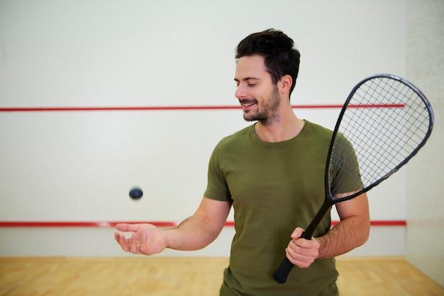 Portret van mannelijke squashspeler met racket op de baan