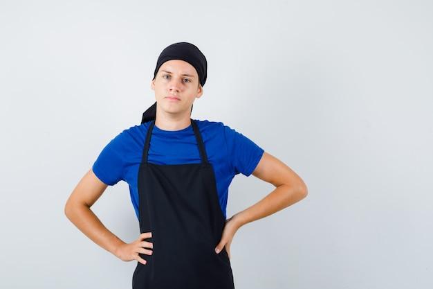 Portret van mannelijke tienerkok met handen op taille in t-shirt, schort en zelfverzekerd vooraanzicht
