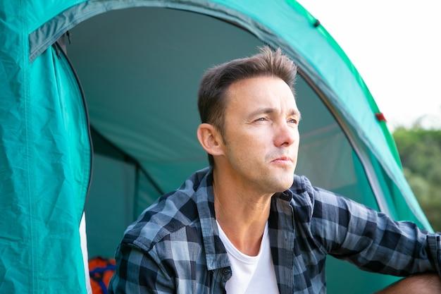 Portret van mannelijke toeristenzitting in tent en wegkijken. jonge kaukasische wandelaars of reiziger die van aard ontspannen en genieten van landschap. backpacken toerisme, avontuur en zomervakantie concept