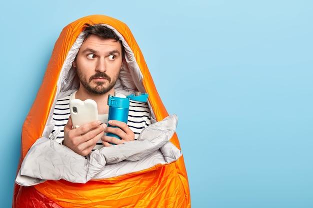 Portret van mannelijke wandelaar verpakt in slaapzak, kijkt bedachtzaam weg, houdt mobiele telefoon en kolf vast, heeft zomervakantie, wordt echte camper