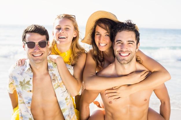 Portret van mannen die op de rug aan vrouwen op het strand geven