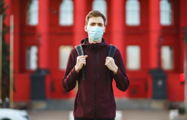 Portret van mannen in beschermend steriel medisch masker op haar gezicht op straatstad. covid19.