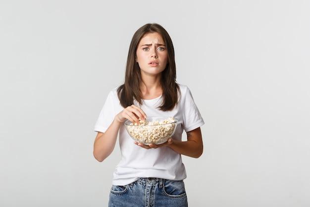 Portret van medelevende jonge vrouw kijken naar hartverwarmende film, popcorn eten.