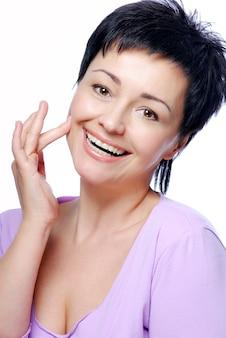 Portret van medio lachende vrouw met een goede conditie van de huid