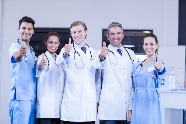 Portret van medisch team die duimen opzetten en in het ziekenhuis glimlachen
