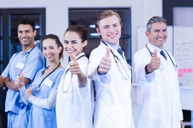 Portret van medisch team die hun duimen opzetten en in het ziekenhuis glimlachen