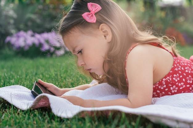 Portret van meisje 3-4 in rode kleren liggend op deken op groen gras en op zoek naar mobiele telefoon. kinderen die gadgets gebruiken