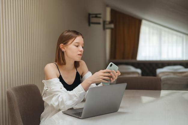 Portret van meisje aan tafel in hotelkamer die op laptop werkt