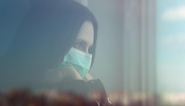 Portret van meisje achter gesloten venster dat beschermend masker draagt en uit met exemplaarruimte kijkt