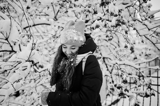 Portret van meisje bij de winter sneeuwdag dichtbij sneeuw behandelde bomen.