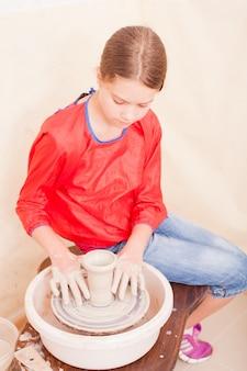 Portret van meisje dat aardewerk probeert te maken van witte klei op een pottenbakkersschijf