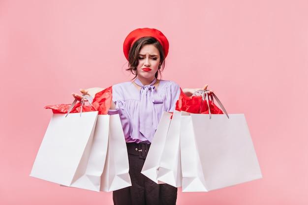 Portret van meisje dat in rode baret ontevreden pakketten met kleren bekijkt. dame in lila blouse en zwarte broek die zich voordeed op roze achtergrond.