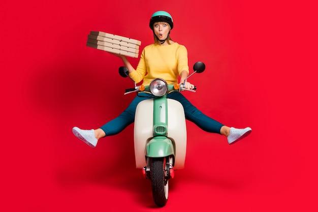 Portret van meisje die bromfiets dragende doospizza berijden op rode muur