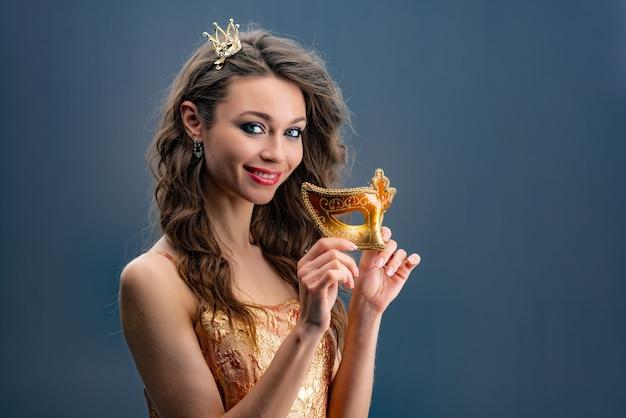 Portret van meisje die speels de camera met een prinseskroon bekijken op haar hoofd en in een gouden kleding.