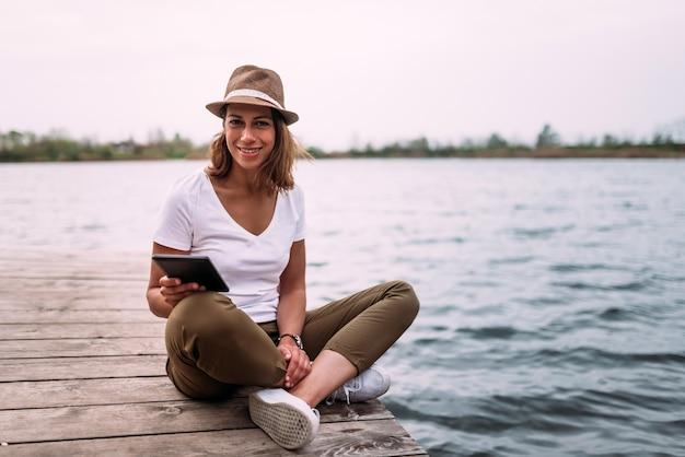 Portret van meisje die tablet gebruiken terwijl het zitten op houten pier.