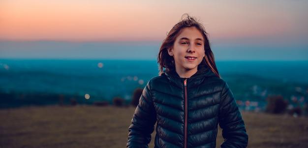 Portret van meisje die zwart jasje dragen bij zonsondergang