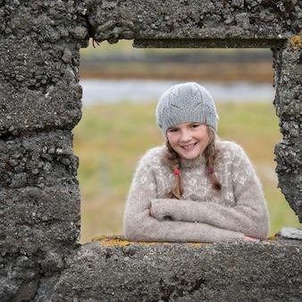 Portret van meisje door het raamkozijn van de rotsmuur