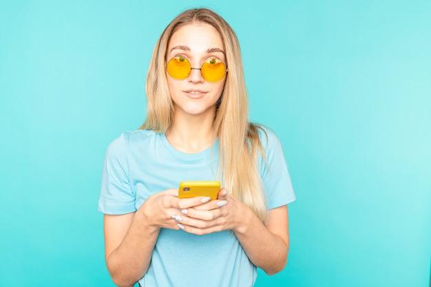 Portret van meisje gebruikt haar smartphone lezen sociale media nieuws schreeuw wow omg geïsoleerd over blauwe kleur.