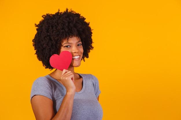 Portret van meisje geïsoleerd met een papieren hart op geel Premium Foto