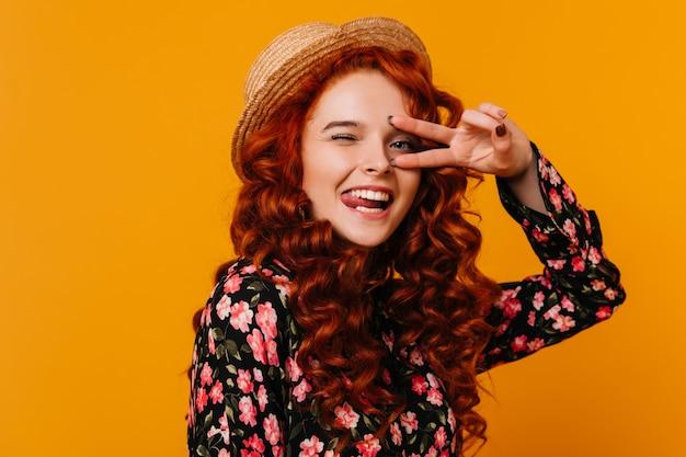 Portret van meisje gek rond op oranje ruimte. dame in bloemenblouse knipoogt en toont vredesteken.
