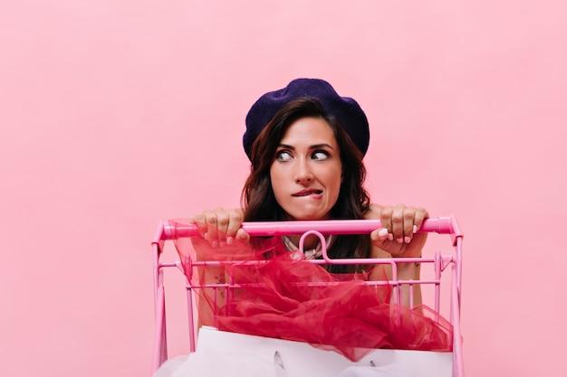 Portret van meisje in baret die van winkelen houdt en kar houdt. vrouw met krullend zwart haar in baret poseren op roze achtergrond.