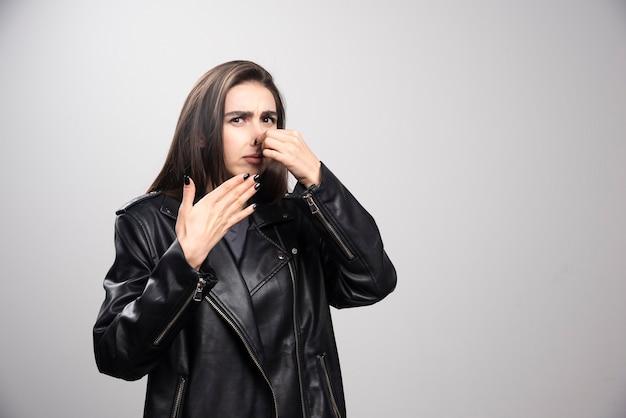 Portret van meisje in casual stijl zwart lederen jas staande haar neus knijpen