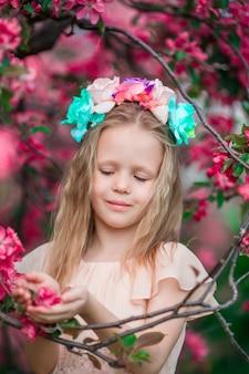 Portret van meisje in mooie bloeiende appeltuin in openlucht