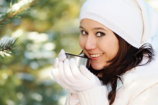 Portret van meisje in witte hoed en handschoenen houdt metalen beker in de buurt van het gezicht, glimlacht en kijkt naar de camera