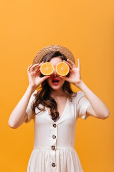 Portret van meisje in witte kleding en hoed die ogen behandelen met de oranje helften.