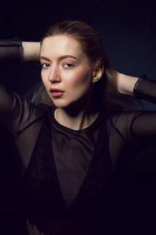Portret van meisje in zwarte lingerie met haar dat naast venster zit