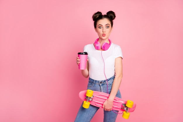 Portret van meisje luisteren muziek drinken latte houd skate board pruillip lippen geïsoleerd over roze achtergrond