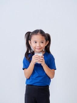 Portret van meisje met glas melk op licht