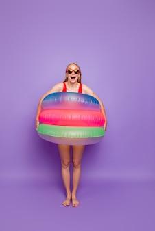Portret van meisje met kleurrijke vlotter rond taille die op violette flotador wordt geïsoleerd