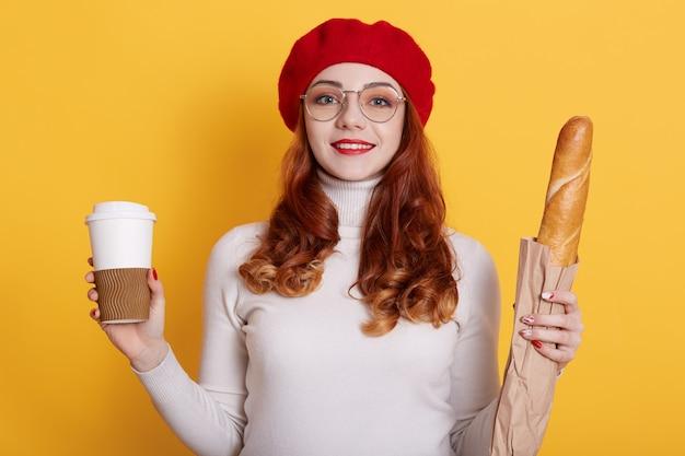 Portret van meisje met lang rood haar die baret, wit overhemd en glazen dragen die brood in document zak houden en koffie op geel weghalen