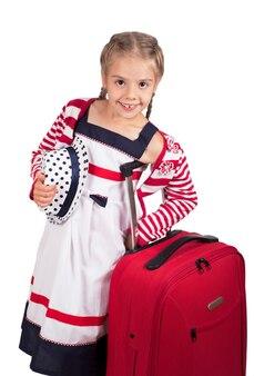Portret van meisje met reiskoffer en hoed op wit wordt geïsoleerd