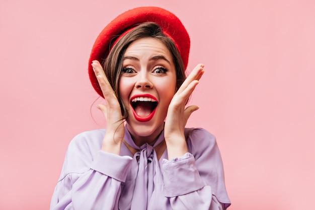 Portret van meisje met rode lippen en groene ogen. dame in baret schreeuwt van geluk.