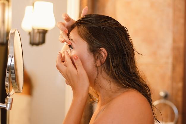 Portret van meisje ooglens toe te passen in de badkamer