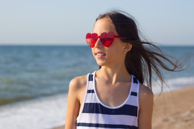 Portret van meisje tegen de achtergrond van de zee en de lucht meisje met een bril in de vorm van een hart