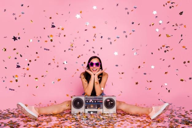 Portret van meisje zittend vloer evenement pailletten vliegen geïsoleerd over roze muur
