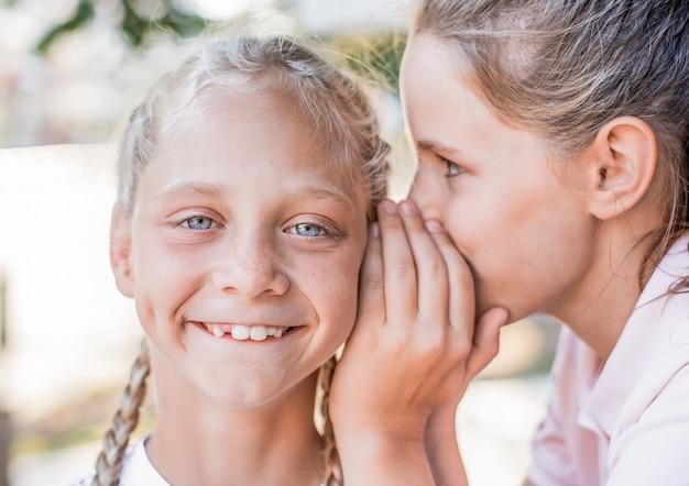 Portret van meisjes die in het geheim in het oor spreken