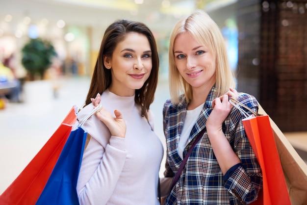 Portret van meisjes met boodschappentassen in winkelcentrum