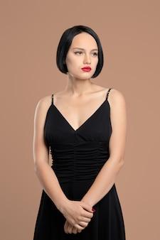 Portret van melancholische dame in jurk met riemen. studio opname op beige