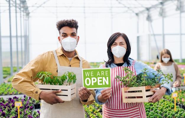 Portret van mensen die in een kas in een tuincentrum werken, winkel open na afsluiting van het coronavirus.