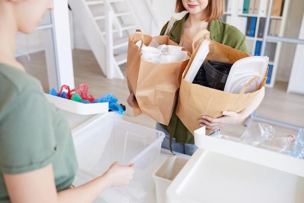 Portret van mensen die plastic thuis sorteren, focus op vrouw met papieren zakken met items klaar voor recycling