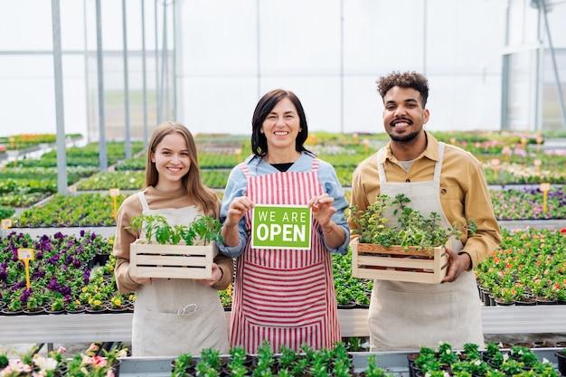 Portret van mensen die werken en kijken naar camera in kas in tuincentrum